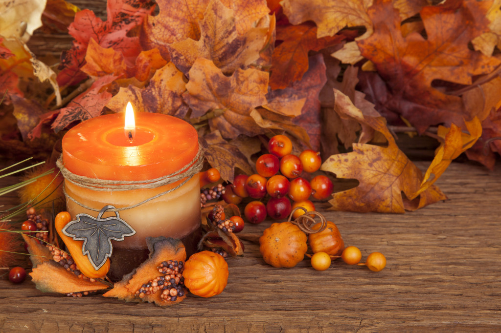Autumn candle over wooden background