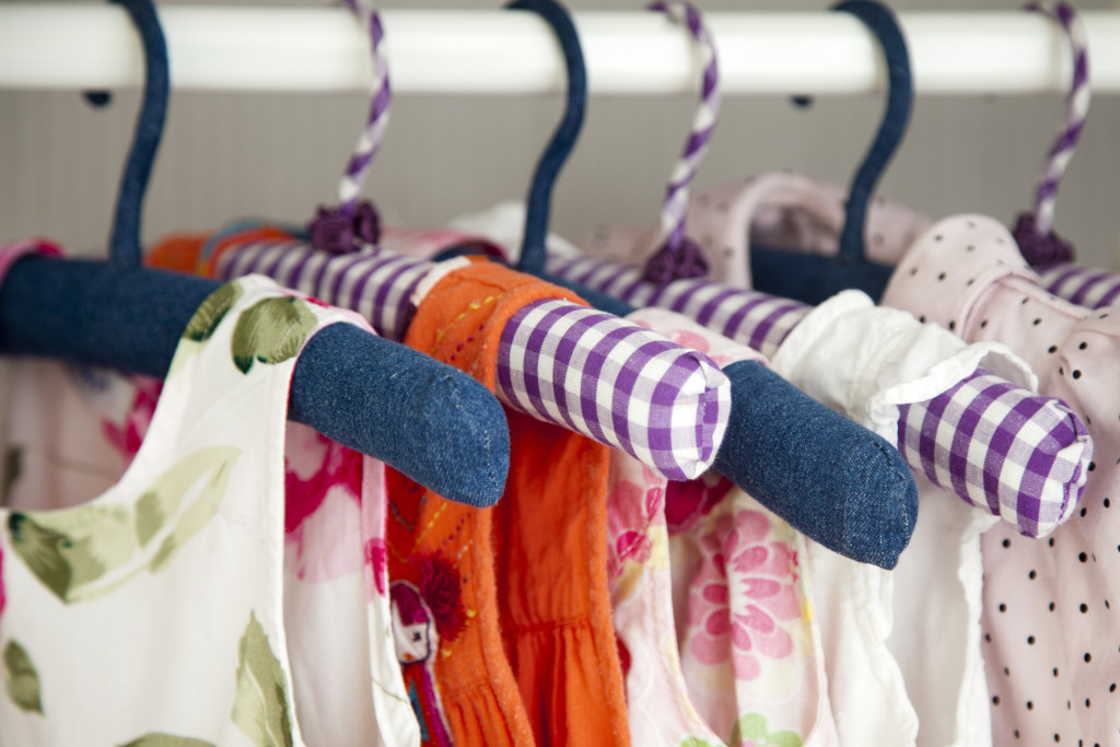 a view inside a baby girl closet where several dresses are hung on hangers
