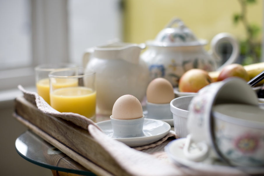 Typical english breakfast. Tea, boiled eggs, fruit and orange juice for two.